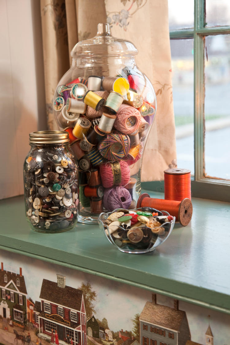 A jar of buttons and thread.