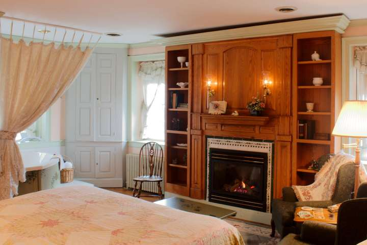 The gas fireplace and bookshelves are seen from across the foot of the king-sized bed.