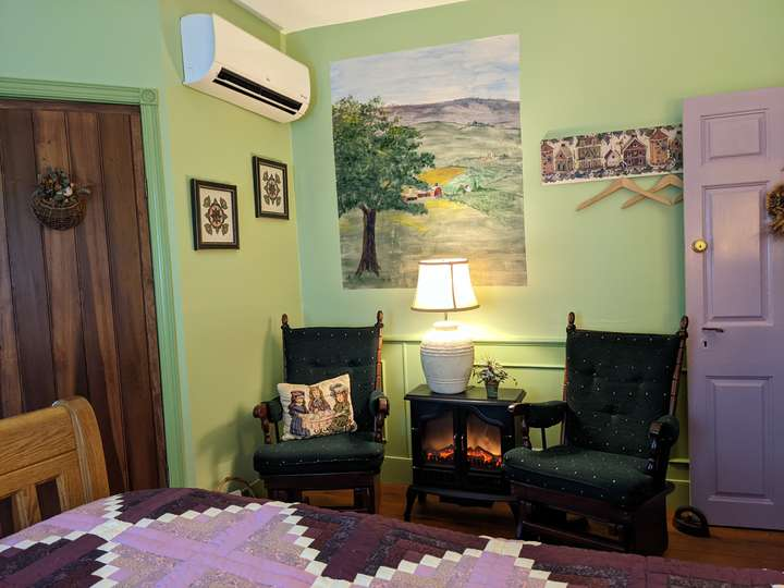 two padded rocking chairs with an electric fireplace in front of a mural of fields
