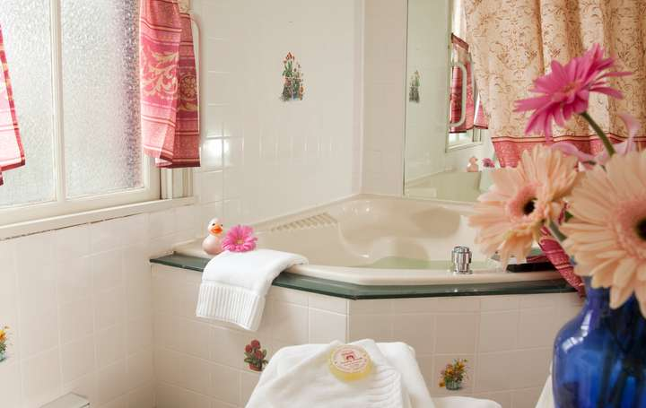 A whirlpool tub with towels and flowers.